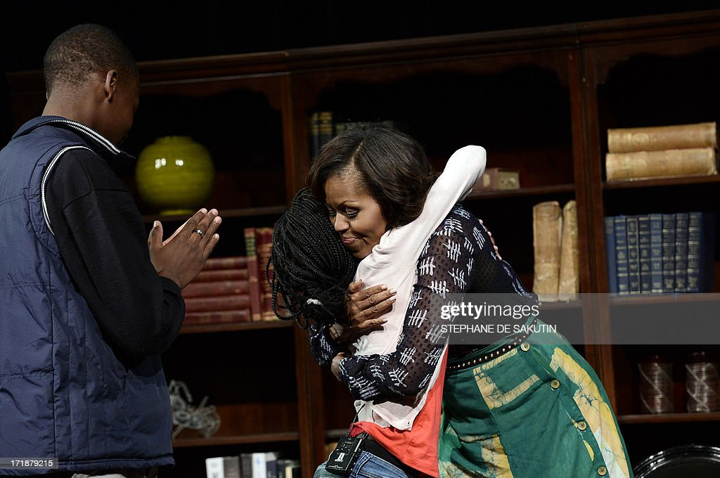 US First Lady Michelle Obama hugs a student during a discussion on June 29, 2013 at the Sci-Bono Discovery Center in Johannesburg. The first lady was joined by teenagers from accross South Africa as well as students joining virtually from cities around the US. This virtual event has been organised in conjunction with African youth and music channel MTV Base and Google + to highlight the importance of education. AFP PHOTO / STEPHANE DE SAKUTIN