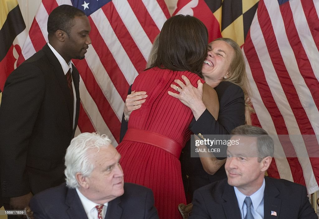 US First Lady Michelle Obama (C) hugs a woman who will benefit from legislation to be signed by Maryland Governor Martin O'Malley (seated R) and Maryland Senate President Mike Miller (seated L) named the Veterans Full Employment Act of 2013, supporting military veterans in licensing, training, education and employment at the Maryland State House in Annapolis, Maryland on April 17, 2013. AFP PHOTO / Saul LOEB