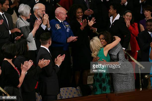 First lady Michelle Obama hugs Dr Jill Biden before the start of US President Barack Obama's State of the Union speech January 20 2015 in Washington...