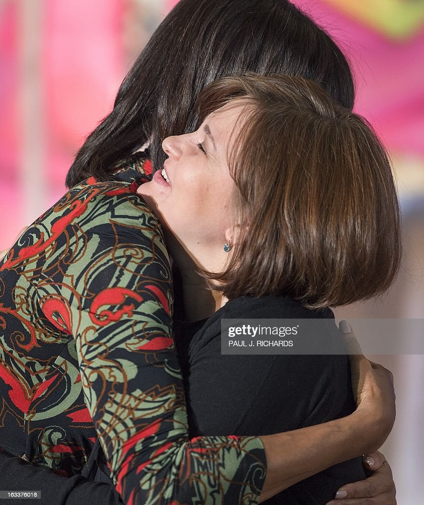 US First Lady Michelle Obama (L) hugs Elena Milashina of Russia after presenting her with the Secretary of State's International Women of Courage Award inside the Dean Acheson Auditorium of the U.S. Department of State March 8, 2013, in Washington. The Secretary of State's International Women of Courage Award annually recognizes women around the globe who have shown exceptional courage and leadership in advocating for women's rights and empowerment, often at great personal risk. Since the inception of this award in 2007, the Department of State has honored 67 women from 45 different countries. AFP Photo/Paul J. Richards