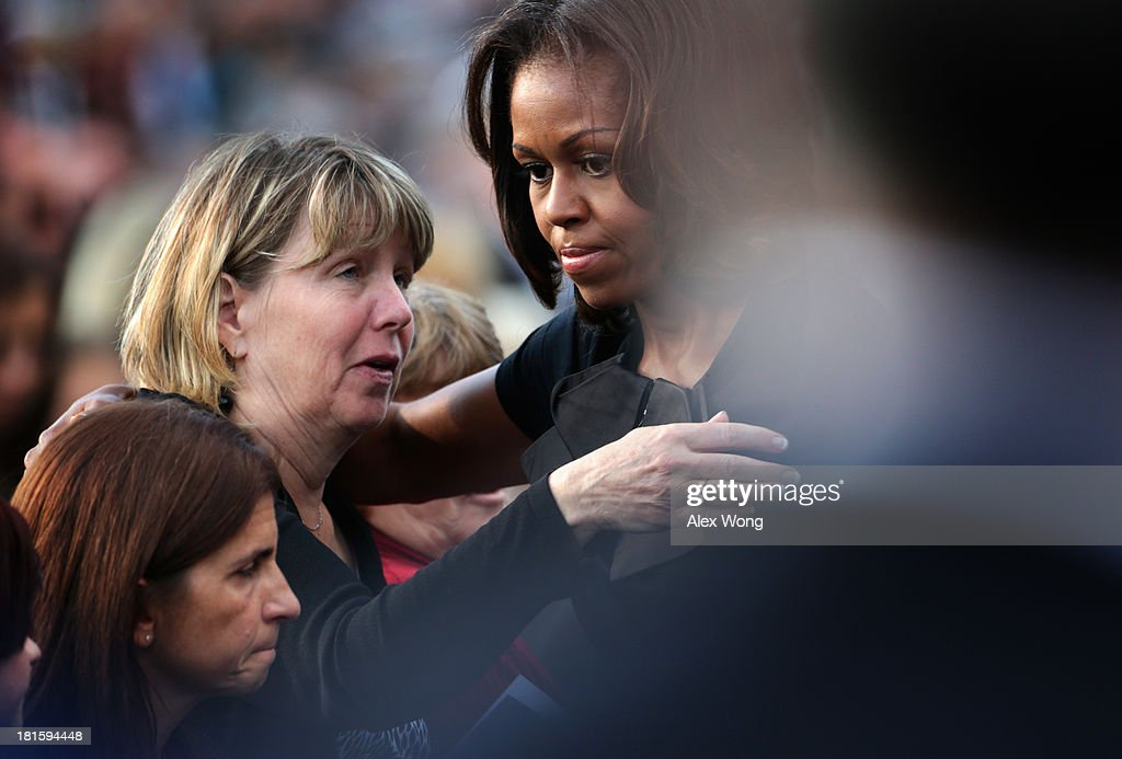 S first lady Michelle Obama hugs family members during a memorial service for victims of the Washington Navy Yard shooting at the Marine Barracks...