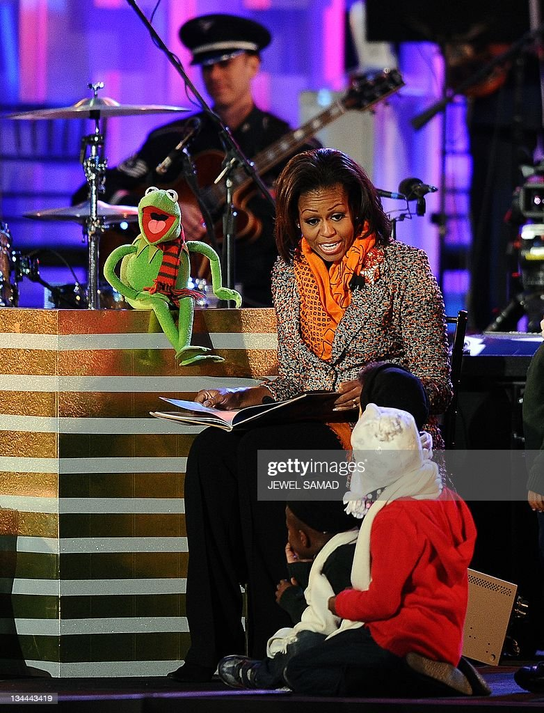 US First Lady Michelle Obama is joined by Kermit the Frog, from the Muppets movie, as she reads a story during the 2011 National Christmas Tree Lighting Ceremony on The Ellipse near the White House in Washington, DC, on December 1, 2011. AFP Photo/Jewel Samad