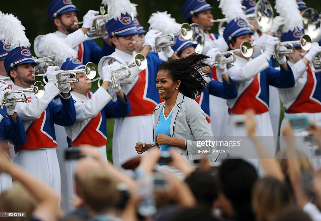 US First Lady Michelle Obama joggs to the stage to speak during 'Let's Move-London' event at the Winfield House in London on July 27, 2012, hours before the official start of the London 2012 Olympic Games.