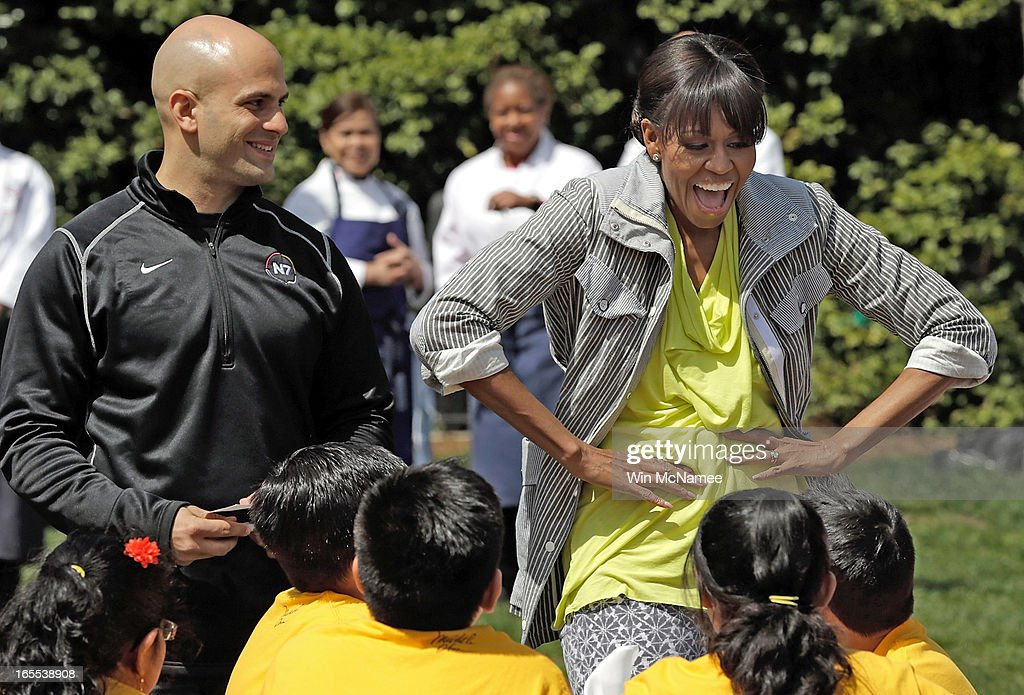 U.S. first lady Michelle Obama jokes with schoolchildren with White House chef Sam Kass (L) after planting the White House Kitchen Garden on the South Lawn of the White House April 4, 2013 in Washington, DC. For the fifth time, the first lady invited students from 'schools that have made exceptional improvements to school lunches' from Florida, Massachusetts, Tennessee and Vermont to help her plant the garden.