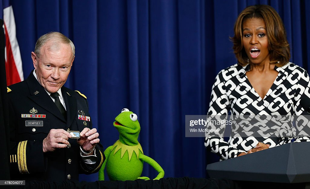U.S. first lady Michelle Obama (R) looks on as Chairman of the Joint Chiefs of Staff Gen. Martin Dempsey presents a special award to Kermit the Frog during a screening of Disney's 'Muppets Most Wanted' at the Eisenhower Executive Office Building March 12, 2014 in Washington, DC. The movie's preview was for an audience of military children and families as part of the Joining Forces Initiative.
