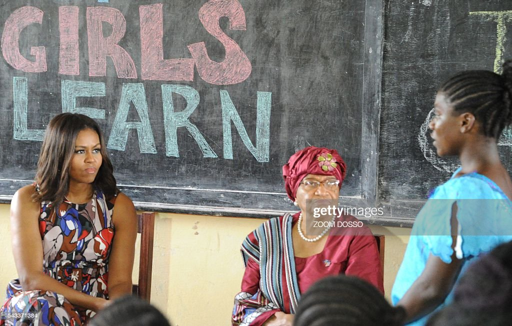 USA first lady Michelle Obama (L) looks on as she visits a woman education program in Monrovia on June 27, 2016. US First Lady Michelle Obama told girls in Liberia on Monday to fight to stay in school, as she visited the west African country where the vast majority drops out due to financial pressures. / AFP / ZOOM