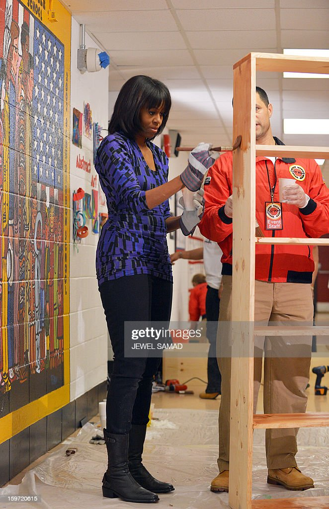 US First Lady Michelle Obama paints a bookshelf at Burrville Elementary School during Day of Service on January 19, 2013 in Washington DC, as part of the 57th Presidential Inauguration. Americans across the country participate in service projects in their communities to celebrate the legacy of civil rights leader Dr. Martin Luther King, Jr. The holiday honoring King will be observed on January 21, the day of the second inauguration of US President Barack Obama and Vice President Biden. AFP PHOTO/Jewel Samad