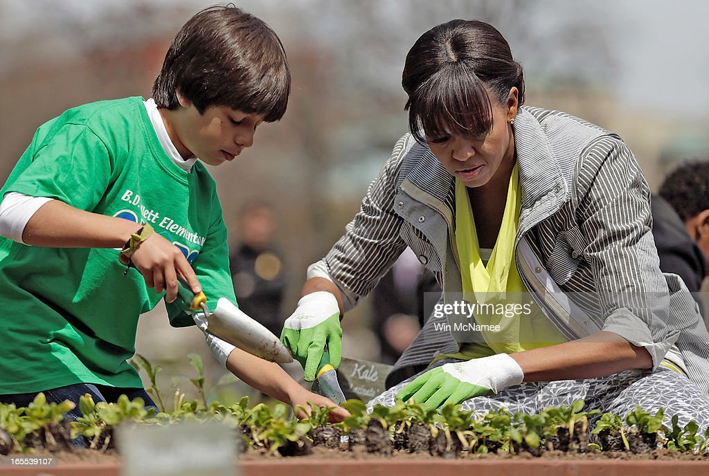 U.S. first lady Michelle Obama plants the White House Kitchen Garden with fifth grader Emilo Vega of Florida on the South Lawn of the White House April 4, 2013 in Washington, DC. For the fifth time, the first lady invited students from 'schools that have made exceptional improvements to school lunches from Florida, Massachusetts, Tennessee and Vermont to help her plant the garden.
