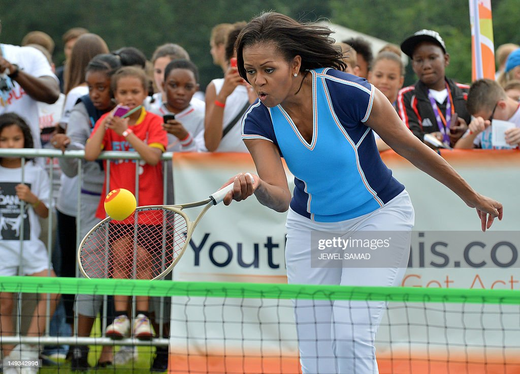 US First Lady Michelle Obama plays tennis during 'Let's Move-London' event at the Winfield House in London on July 27, 2012, hours before the start of the London 2012 Olympic Games.