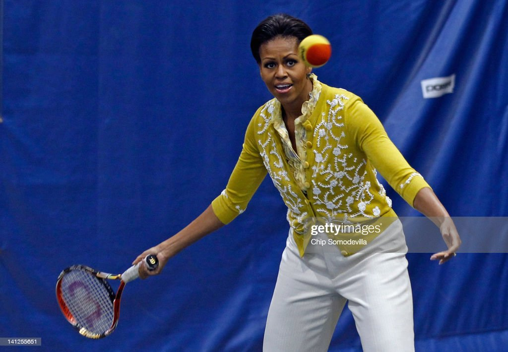 U.S. First Lady <a gi-track='captionPersonalityLinkClicked' href=/galleries/search?phrase=Michelle+Obama&family=editorial&specificpeople=2528864 ng-click='$event.stopPropagation()'>Michelle Obama</a> plays tennis with students during an Olympics-themed event with area school children at American University March 13, 2012 in Washington, DC. Fifth graders from MacFarland Middle School in Washington, D.C., Manor View Elementary School in Maryland and Arlington Science Focus School in Virginia participated in a mini-Olympics competition in celebration of the 2012 London Summer Olympics and the first lady's Let's Move! initiative.