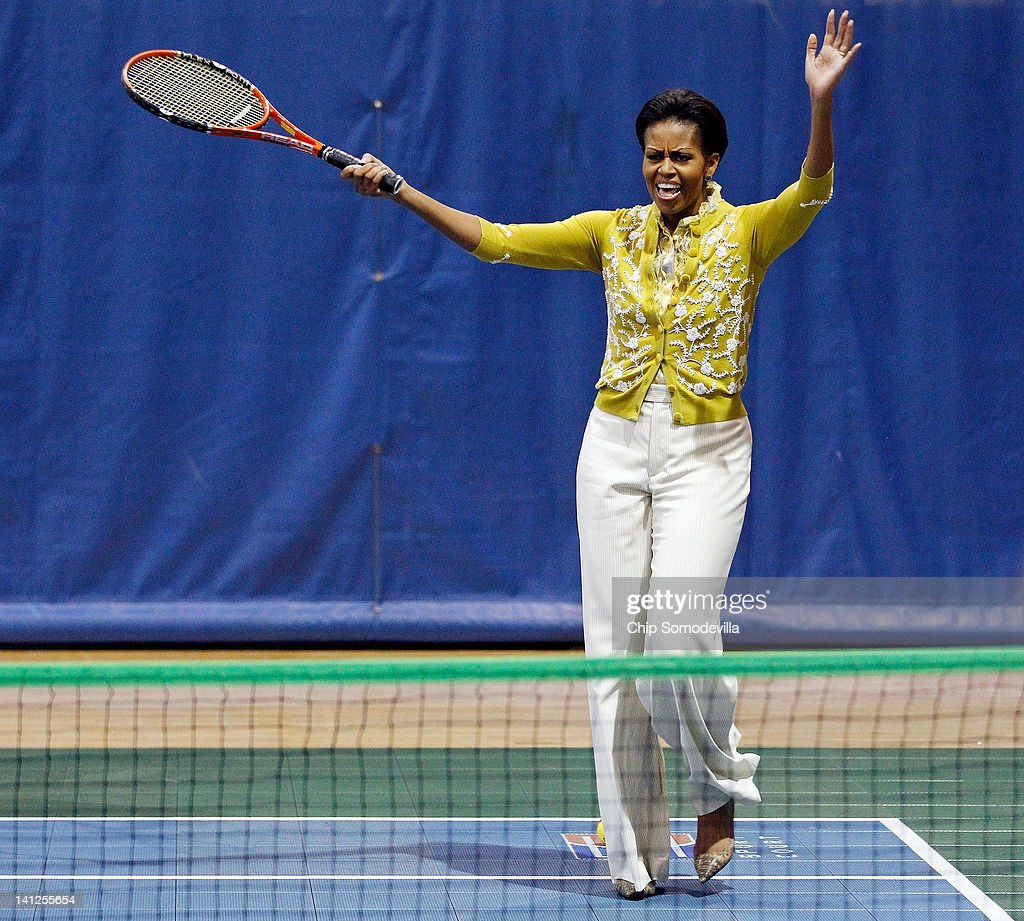 U.S. First Lady <a gi-track='captionPersonalityLinkClicked' href=/galleries/search?phrase=Michelle+Obama&family=editorial&specificpeople=2528864 ng-click='$event.stopPropagation()'>Michelle Obama</a> plays tennis with students during an Olympics-themed event with area school children at American University March 13, 2012 in Washington, DC. Fifth graders from MacFarland Middle School in Washington, D.C., Manor View Elementary School in Maryland and Arlington Science Focus School in Virginia participated in a mini-Olympics competition in celebration of the 2012 London Summer Olympics and Mrs. Obama's Let's Move! initiative.