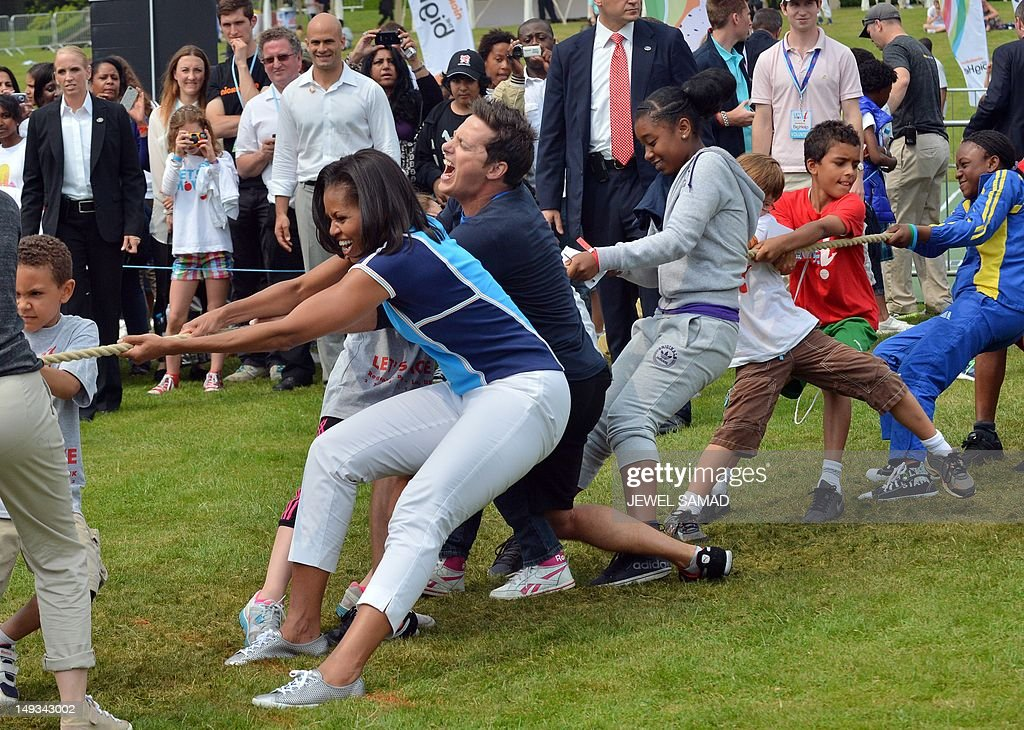US First Lady Michelle Obama (C) plays tug-of-war during 'Let's Move-London' event at the Winfield House in London on July 27, 2012, hours before the start of the London 2012 Olympic Games. AFP PHOTO/ JEWEL SAMAD