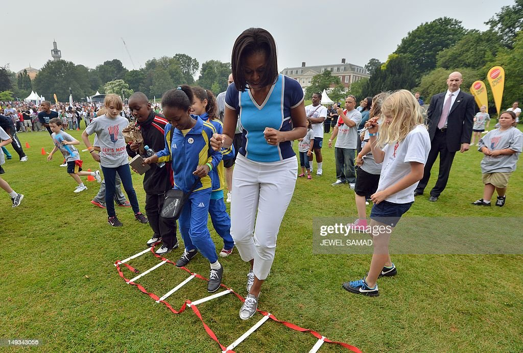 US First Lady Michelle Obama plays with children as part of her 'Let's Move-London' event at the Winfield House in London on July 27, 2012, hours before the official start of the London 2012 Olympic Games. AFP PHOTO / JEWEL SAMAD