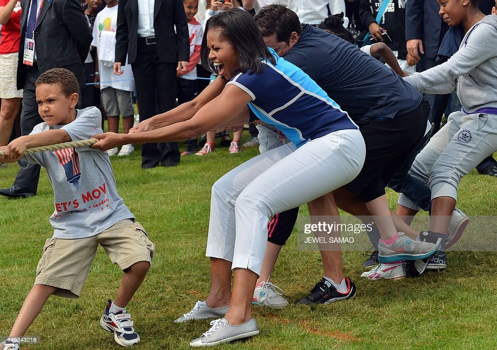 US First Lady Michelle Obama plays with children as part of her 'Let's Move-London' event at the Winfield House in London on July 27, 2012, hours before the official start of the London 2012 Olympic Games. AFP PHOTO/ JEWEL SAMAD
