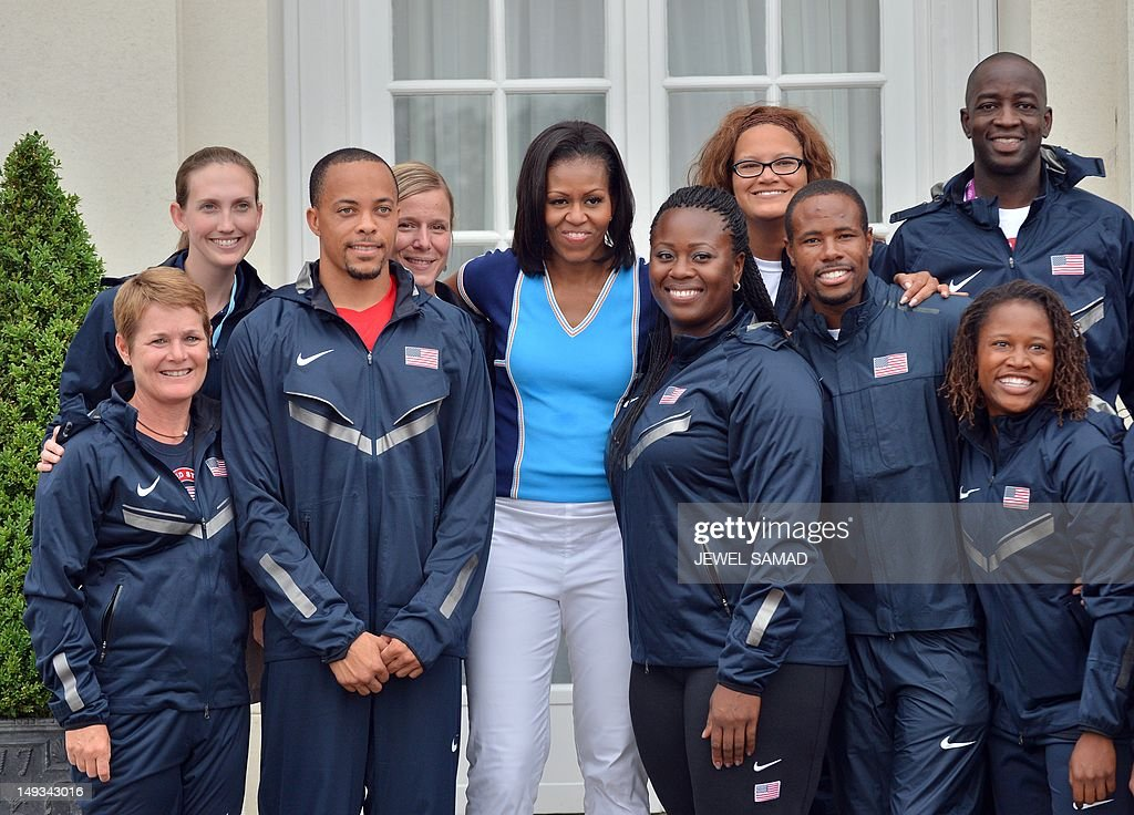 US First Lady Michelle Obama poses with US athlete team members during 'Let's Move-London' event at the Winfield House in London on July 27, 2012, hours before the start of the London 2012 Olympic Games. AFP PHOTO/ JEWEL SAMAD