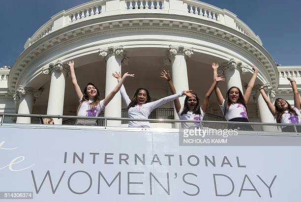US First Lady Michelle Obama poses with young female students in front of the White House in Washington DC on March 8 2016 before an event to mark...