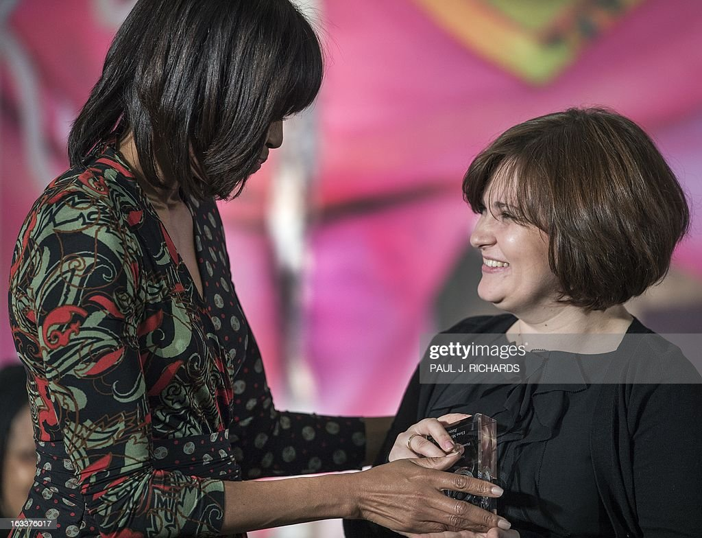 US First Lady Michelle Obama (L) presents Elena Milashina of Russia with the Secretary of State's International Women of Courage Award inside the Dean Acheson Auditorium of the US Department of State March 8, 2013, in Washington. The Secretary of State's International Women of Courage Award annually recognizes women around the globe who have shown exceptional courage and leadership in advocating for women's rights and empowerment, often at great personal risk. Since the inception of this award in 2007, the Department of State has honored 67 women from 45 different countries. AFP Photo/Paul J. Richards