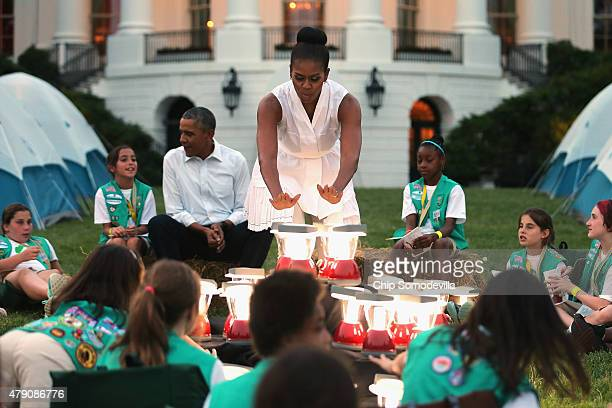 S first lady Michelle Obama pretends to warm herself over a 'fire' made from batterypowered lanterns as she and President Barack Obama host a group...