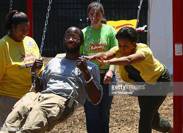 S first lady Michelle Obama pushes a fellow volunteer in a swing while helping to construct a playground at the Imagine Southeast Public Charter...