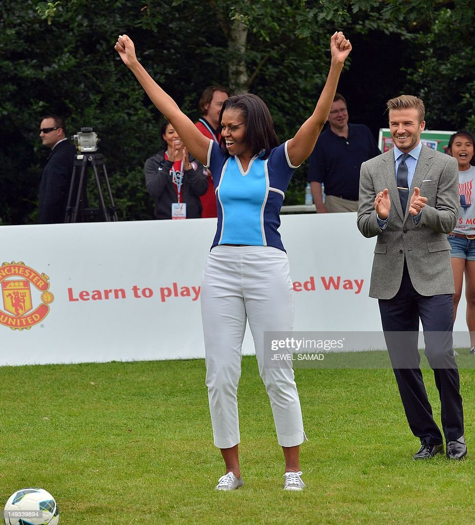 US First Lady Michelle Obama raises her arms as British footballer David Beckham (R) applauds during a football game with children as part of the 'Let's Move-London' event at the Winfield House in London on July 27, 2012, hours before the official start of the London 2012 Olympic Games. AFP PHOTO / JEWEL SAMAD