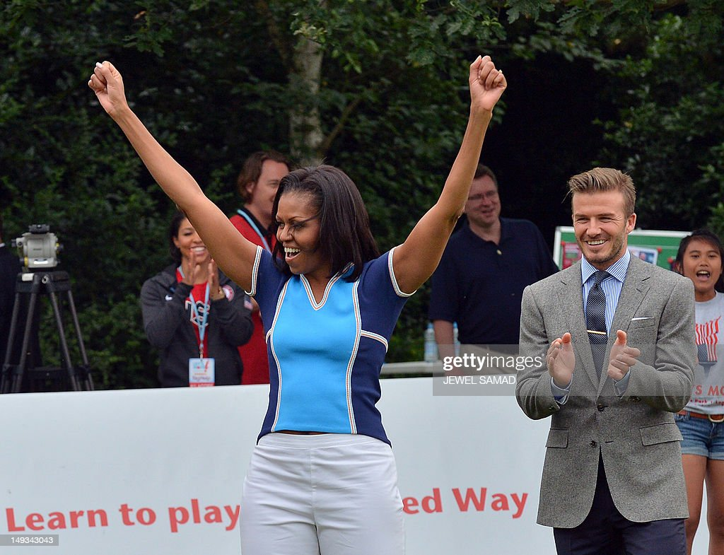 First Lady Michelle Obama raises her arms as British footballer David Beckham (R) applauds during a football game with children as part of the 'Let's Move-London' event at the Winfield House in London on July 27, 2012, hours before the official start of the London 2012 Olympic Games. AFP PHOTO / JEWEL SAMAD