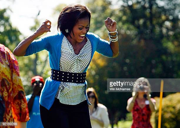 S first lady Michelle Obama reacts as she jump ropes 'Double Dutch' on the South Lawn of the White House during an event promoting exercise and...