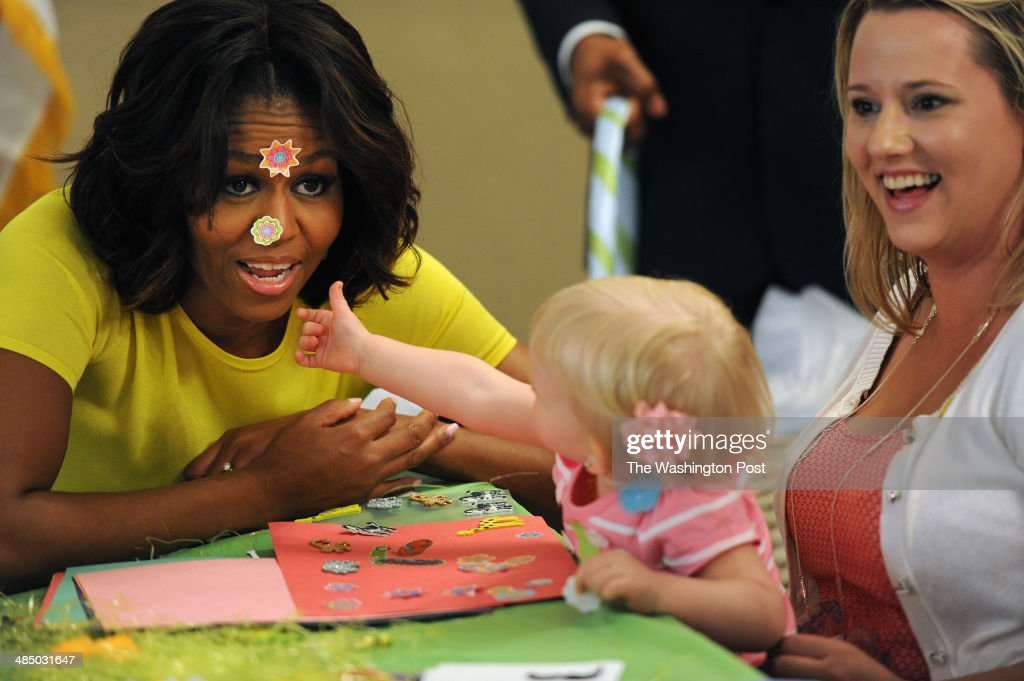 First Lady Michelle Obama reacts to having stickers put on her face by Lilly Oppelt, 1, as she is held by her mother, Amy Oppelt of South Bend, IN as the First Lady visits with families at the Fisher House on the grounds of Walter Reed National Military Medical Center on Monday April 14, 2014 in Bethesda, MD. Lilly's father, U.S. Army Sgt. Lucas Oppelt is being treated at the medical center. Fisher House offers military families a place to stay while a family member receives medical care.