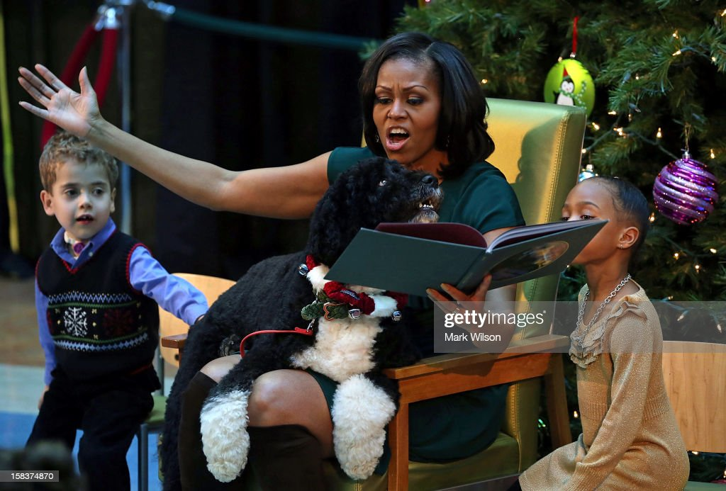 First Lady <a gi-track='captionPersonalityLinkClicked' href=/galleries/search?phrase=Michelle+Obama&family=editorial&specificpeople=2528864 ng-click='$event.stopPropagation()'>Michelle Obama</a> reads a Christmas story as her dog Bo sits on her lap and 5-year-old AJ Murray (L), and 5-year-old Jordyn Akyoko sit nearby at Children's National Medical Center on December 14, 2012 in Washington, DC. The first lady toured the hospital before greeting 200 patients and hospital staff.
