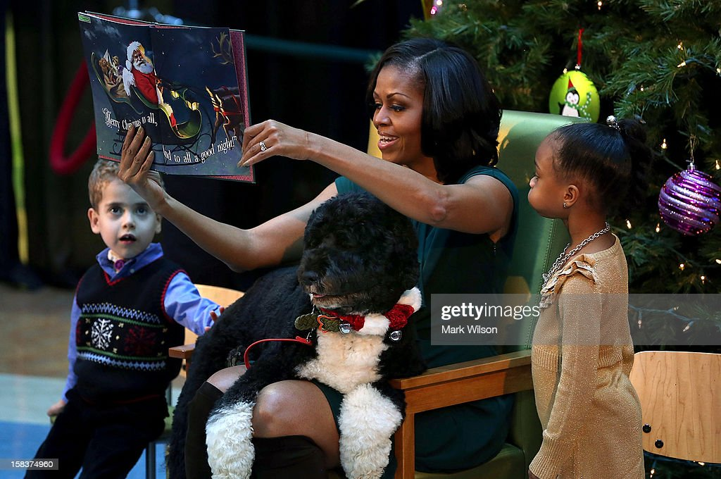 First Lady <a gi-track='captionPersonalityLinkClicked' href=/galleries/search?phrase=Michelle+Obama&family=editorial&specificpeople=2528864 ng-click='$event.stopPropagation()'>Michelle Obama</a> reads a Chritmas story while her dog Bo sits on her lap and 5-year-old AJ Murray (L), and 5-year-old Jordyn Akyoko sit nearby at Children's National Medical Center on December 14, 2012 in Washington, DC. The first lady toured the hospital before greeting 200 patients and hospital staff.
