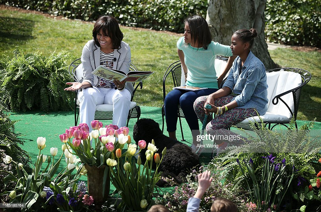 U.S. first lady Michelle Obama (L) reads the story 'Cloudy with a Chance of Meatballs' to children as daughters Sasha (R) and Malia (2nd L) look on during the annual White House Easter Egg Roll on the South Lawn of the White House April 1, 2013 in Washington, DC. President Barack Obama and first lady Michelle Obama hosted thousands of people during the annual celebration of Easter.