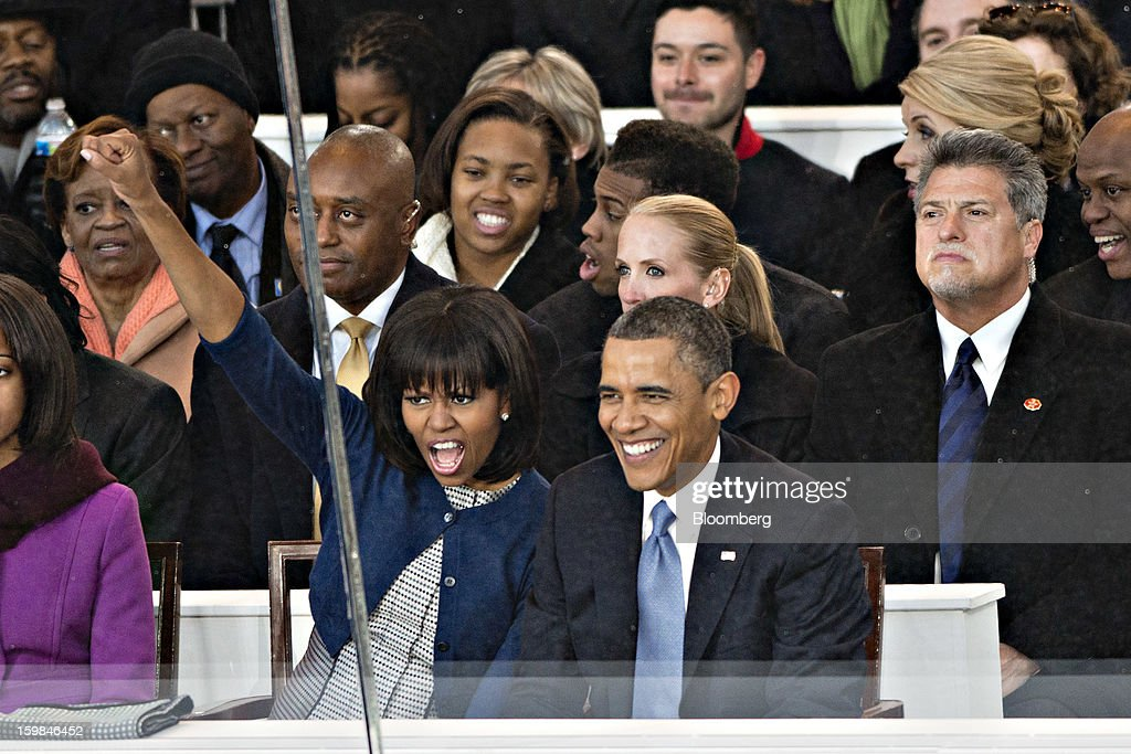 First lady Michelle Obama responds to the crowd yelling 'Fired Up, Ready to Go' while U.S. President Barack Obama smiles while viewing the parade during the inauguration in Washington, D.C., U.S., on Monday, Jan. 21, 2013. A crowd estimated by police to be as large as 700,000, including warmly dressed women with American flags stuck in their hair, a smattering of celebrities and many Republicans, gathered today to witness Obama take his second oath of office on the steps of the U.S. Capitol. Photographer: Daniel Acker/Bloomberg via Getty Images