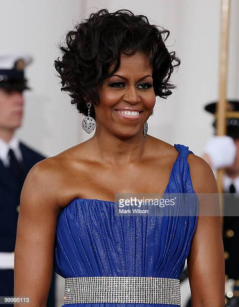 First lady Michelle Obama smiles as she and her husband US President Barack Obama wait for Mexican President Felipe Calderon and his wife Margarita...