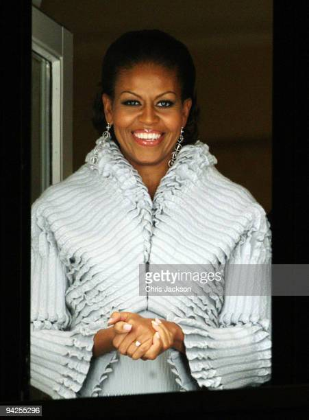 First lady Michelle Obama smiles from behind bullet proof glass on the balcony of the Grand Hotel after waving to the crowds who had gathered outside...