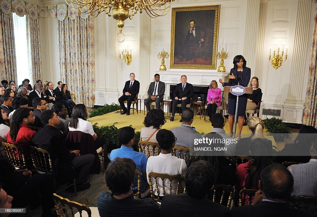 "First Lady Michelle Obama speaks at the start of a student workshop with the cast and crew of the film ""42"" on April 2, 2013 in the State Dining Room of the White House in Washington, DC. From left: screenwriter Brian Helgeland, actor Chadwick Boseman, who plays Jackie Robinson, actor Harrison Ford, who plays Major League Baseball executive Branch Rickey, Rachel Robinson, widow of Jackie Robinson, and Director of the White House Office of Public Engagement Paulette Aniskoff. The movie is the life story of US baseball player Jackie Robinson. AFP PHOTO/Mandel NGAN"