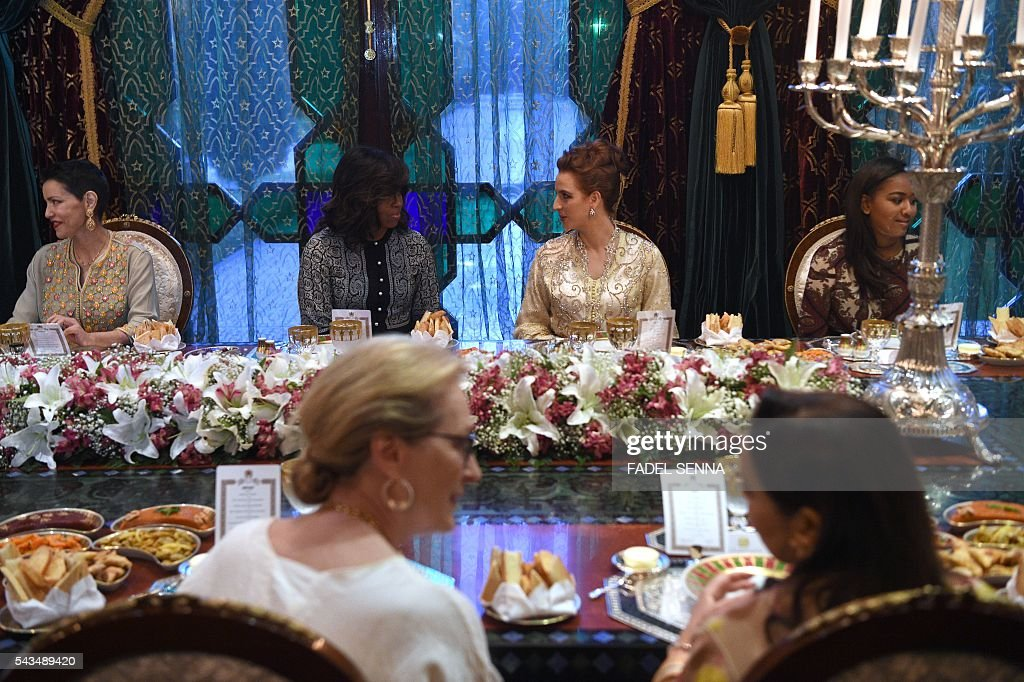 US first lady Michelle Obama (C-L) speaks with Princess Lalla Salma of Morocco (C-R) during a dinner in Marrakech, on June 28, 2016. US First Lady Michelle Obama launched a $100 million aid package in Morocco on June 28, 2016 to promote the education of girls in a country where half of females over 15 are illiterate. Visiting Marakech with actresses Meryl Streep and Frieda Pinto of the 'Slumdog Millionaire' film, she told girls in attendance she wanted them to be part of a global conversation on female education. SENNA