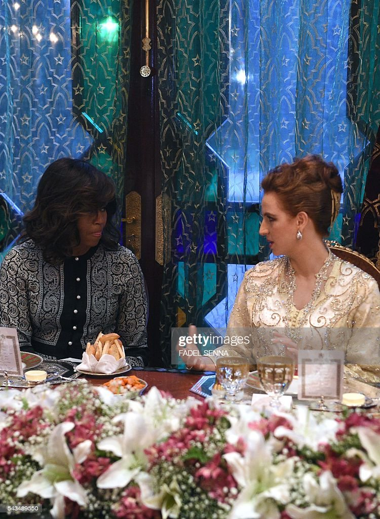 US first lady Michelle Obama (L) speaks with Princess Lalla Salma of Morocco (R) during a dinner in Marrakech, on June 28, 2016. US First Lady Michelle Obama launched a $100 million aid package in Morocco on June 28, 2016 to promote the education of girls in a country where half of females over 15 are illiterate. Visiting Marakech with actresses Meryl Streep and Frieda Pinto of the 'Slumdog Millionaire' film, she told girls in attendance she wanted them to be part of a global conversation on female education. SENNA