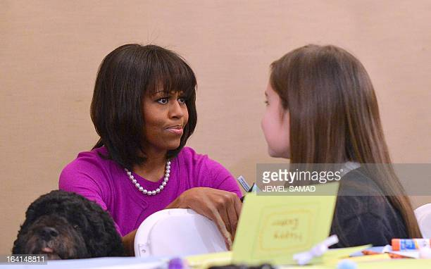 US First Lady Michelle Obama speaks with Sophia Monte as First Family dog Bo looks over a table as the First Lady participates in a preEaster...