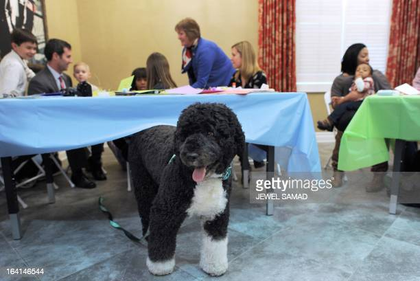 US First Lady Michelle Obama speaks with the Monte Family as First Family dog Bo wonders under a table during preEaster celebration with military...