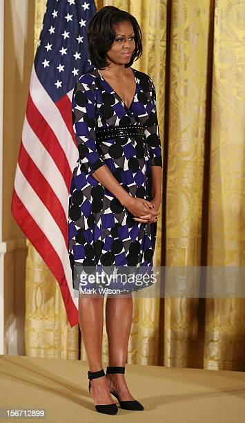 First lady Michelle Obama stands on stage during an awards ceremony for the President's Committee on the Arts and the Humanities in the East Room at...