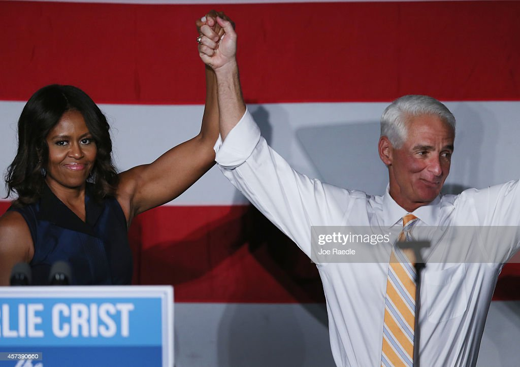 First Lady <a gi-track='captionPersonalityLinkClicked' href=/galleries/search?phrase=Michelle+Obama&family=editorial&specificpeople=2528864 ng-click='$event.stopPropagation()'>Michelle Obama</a> stands with former Florida Governor and now Democratic gubernatorial candidate <a gi-track='captionPersonalityLinkClicked' href=/galleries/search?phrase=Charlie+Crist&family=editorial&specificpeople=753543 ng-click='$event.stopPropagation()'>Charlie Crist</a> as she campaigns for him during an event at the Betty T. Ferguson Recreational Complex Gymnasium on October 17, 2014 in Miami Gardens, Florida. Crist is facing off against incumbent Republican Governor Rick Scott in the November 4, 2014 election