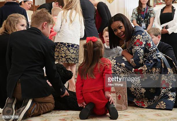S first lady Michelle Obama talks to a little girl as first dog Sunny looks on in the State Dining Room as she hosts military families to the White...