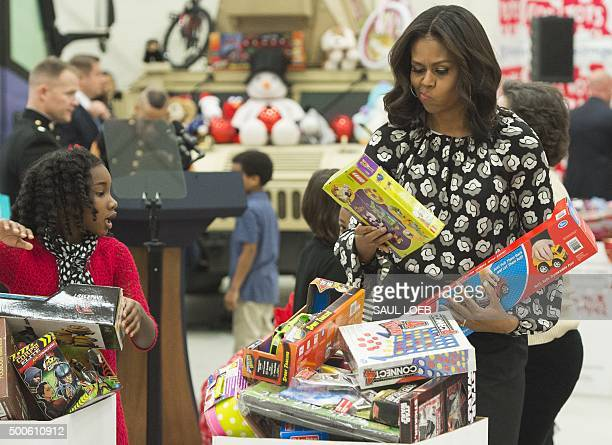 US First Lady Michelle Obama tries to decide which box to use as she sorts toys and gifts donated by the Executive Office of the President staff to...