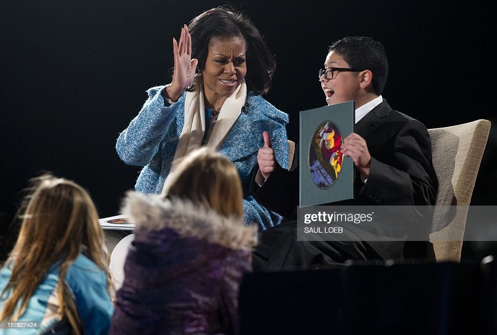 First Lady Michelle Obama tries to high five actor Rico Rodriguez (R) from the televison show 'Modern Family' after they read 'Twas the Night Before Christmas' during the National Christmas Tree Lighting on the Ellipse adjacent to the White House in Washington, DC, on December 6, 2012. The annual event, hosted by Harris, features US President Barack Obama and performances by Jason Mraz, Ledisi, James Taylor, Kenny 'Babyface' Edmonds, Colbie Caillat and American Idol season 11 winner Phillip Phillips. AFP PHOTO / Saul LOEB