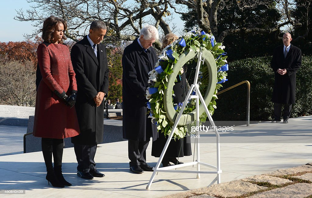First lady Michelle Obama, U.S. President Barack Obama and former U.S. President Bill Clinton lay a wreath at the grave site for President John F. Kennedy at Arlington National Cemetery November 20, 2013 in Arlington, Virginia. The 50th anniversary of the assassination of John F. Kennedy will be marked on November 22.