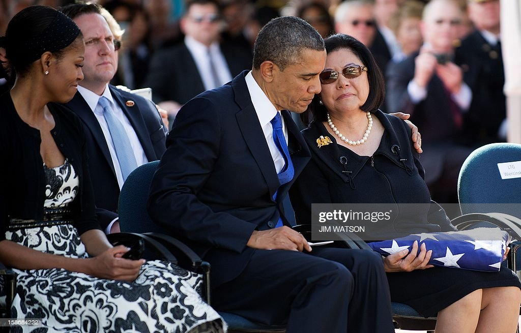 First Lady Michelle Obama (L) watches as US President Barack Obama (C) hugs widow Irene Hirano Inouye (R) as they attend the memorial service for the late Senator Daniel Inouye at the National Memorial Cremetary of the Pacific in Honolulu, Hawaii, December 23, 2012. AFP Photo/Jim WATSON