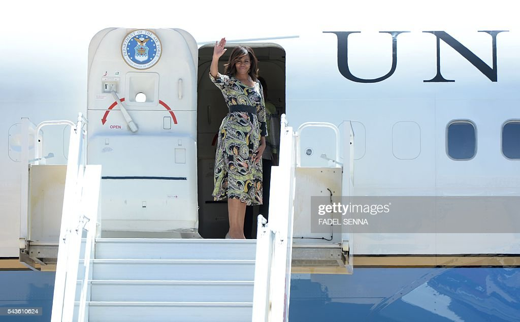 US first lady Michelle Obama waves as she boards her plane prior to departure from the Moroccan city of Marrakesh, on June 29, 2016. The US first lady launched a $100 million aid package in Morocco to promote the education of girls in a country where half of females over 15 are illiterate. Obama, who was accompanied by her daughters Malia and Sasha, arrived on June 27 evening and was welcomed by King Mohamed VI. / AFP / FADEL
