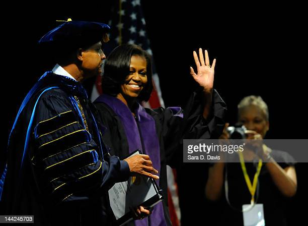 S First Lady Michelle Obama waves to the graduates as she walks across the stage with Chancellor Harold Martin at the North Carolina Agricultural and...
