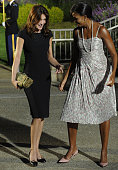 US First Lady Michelle Obama welcomes French President Nicolas Sarkozy's wife Carla Bruni to the G20 dinner at the Phipps Conservatory on September...