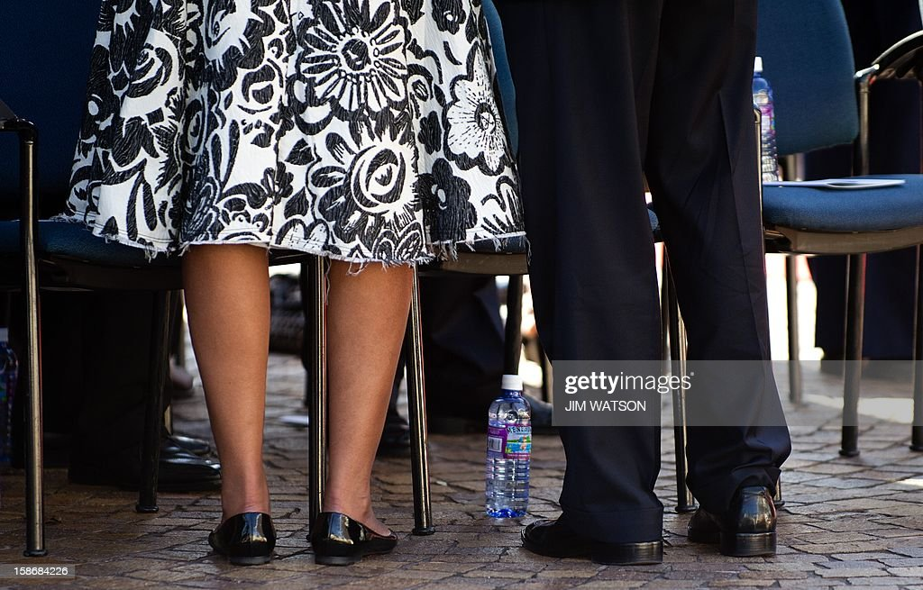 First Lady Michelle Obama's (L) dress hem as she attends the memorial service for the late Senator Daniel Inouye at the National Memorial Cremetary of the Pacific in Honolulu, Hawaii, December 23, 2012 with US President Barack Obama (R). AFP Photo/Jim WATSON