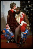 First lady Nancy Reagan sitting on lap kissing Mr T done up as Santa Claus at WH Christmas decoration tour